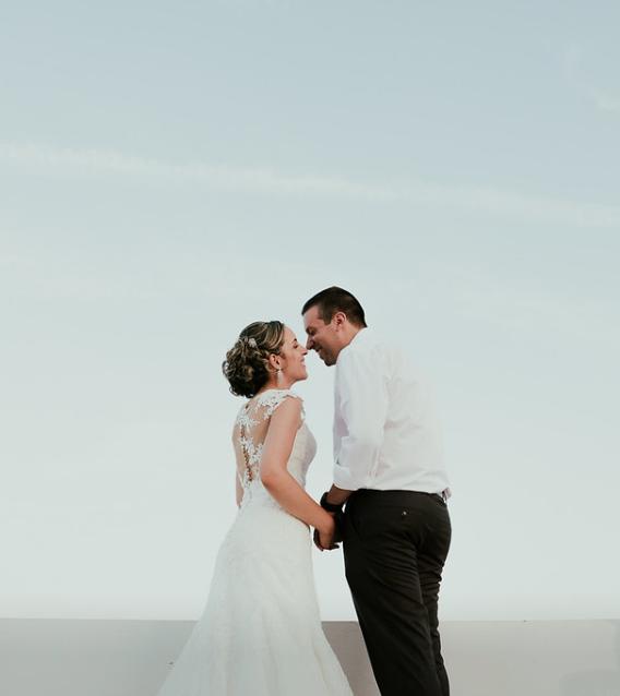 noivos dão mãos sobre fundo azul em casamento em setubal